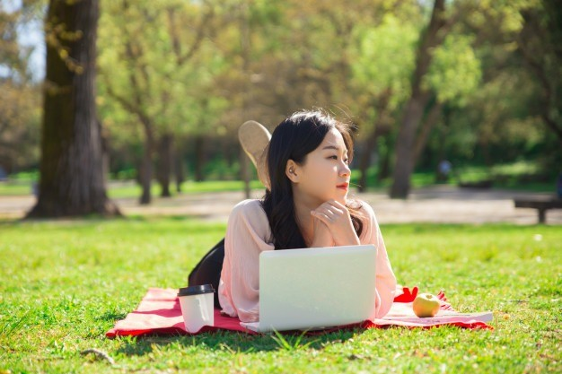 pensive-asian-woman-working-laptop-computer-lawn_1262-18889.jpg
