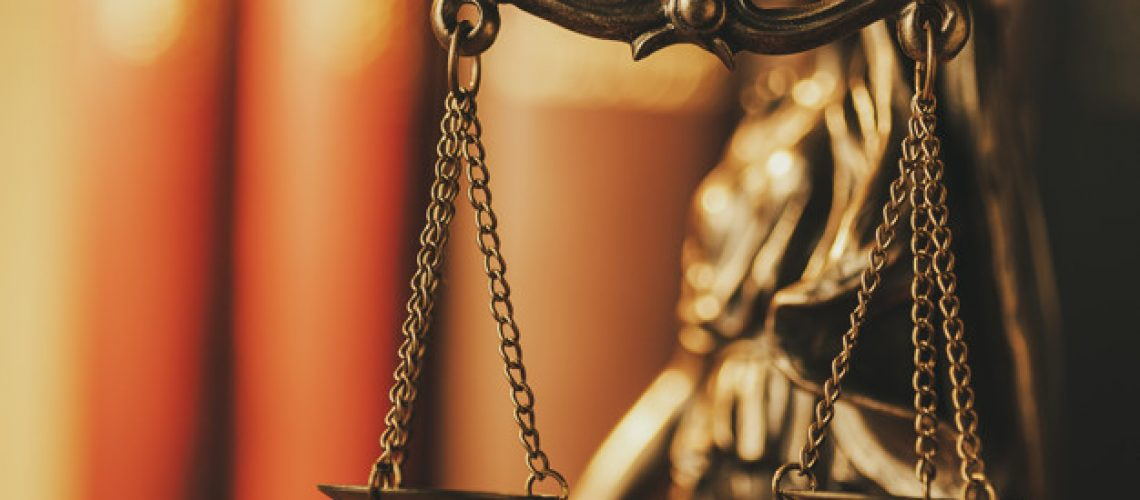 Brass Scales of Justice in a close up view over a coppery background with copy space