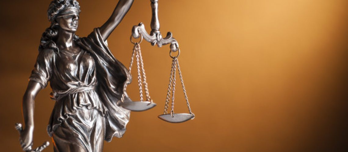 Bronze statue of Justice carrying a sword and holding up scales representing law and order over a brown background with copy space