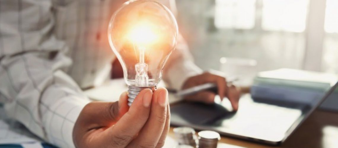business-woman-hand-holding-lightbulb-with-coins-stack-desk_34152-1804