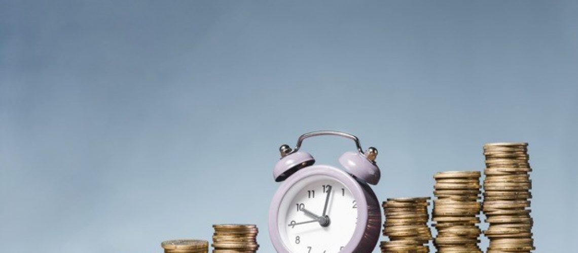 purple-alarm-clock-stack-increasing-coins-wooden-desk-against-blue-background_23-2147943419