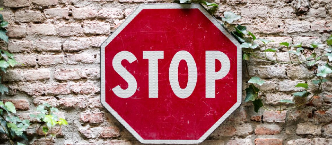 stop-road-sign-attached-brick-wall_126745-213