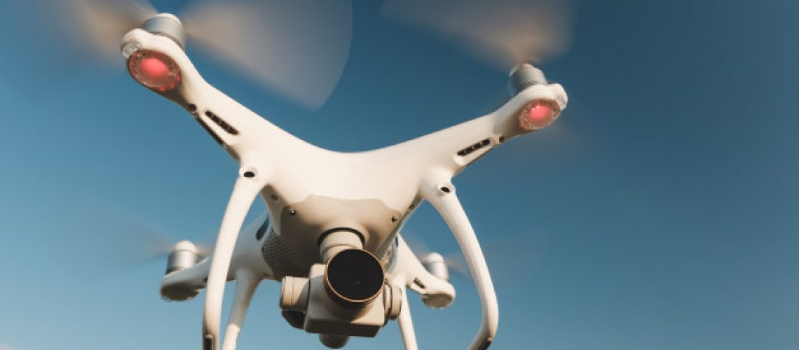 white-drone-hovering-bright-blue-sky_158595-3345